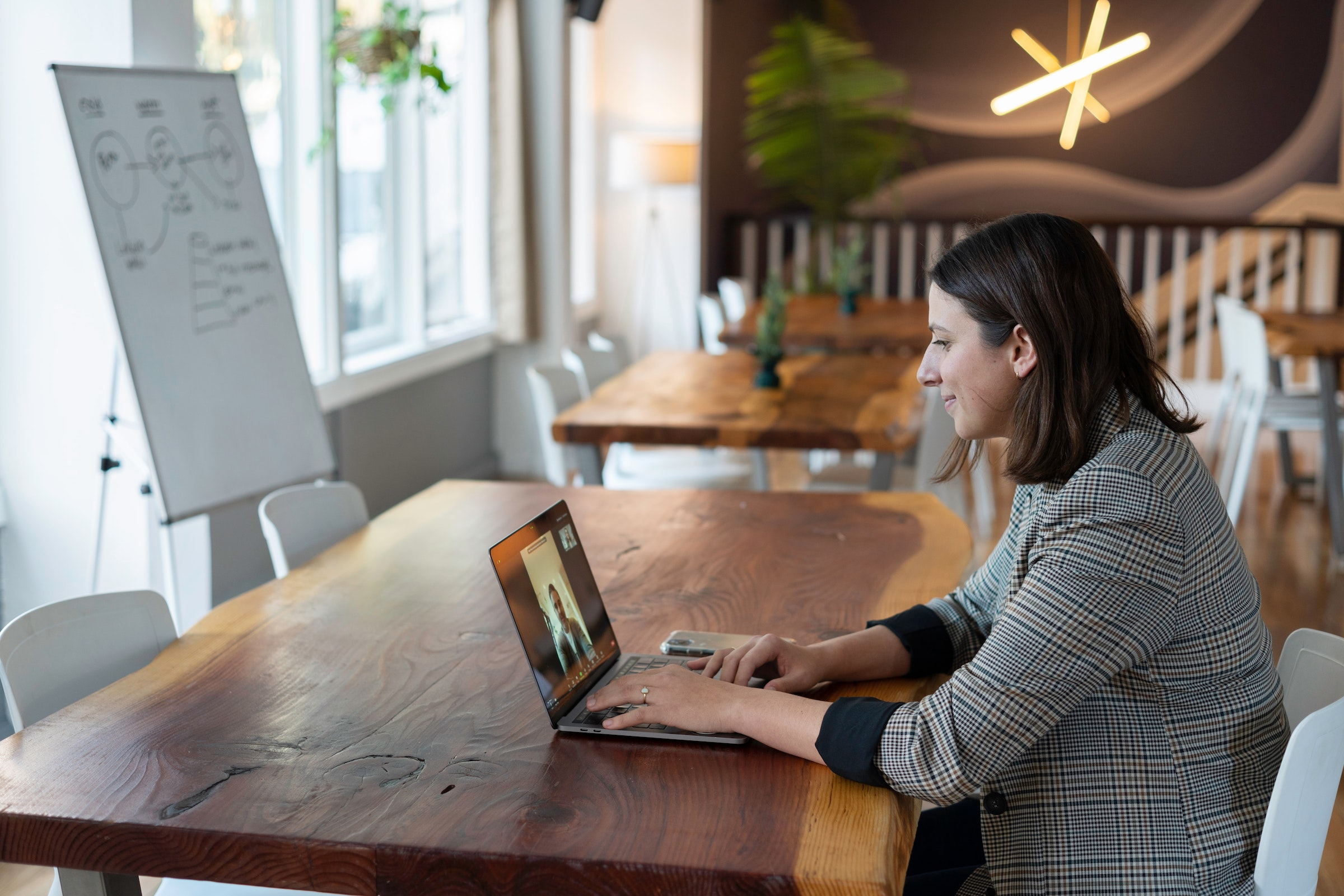 woman participating in live televideo interviews on laptop in an office